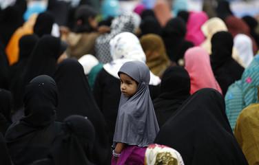 A girl looks on as Muslim women pray in Colombo