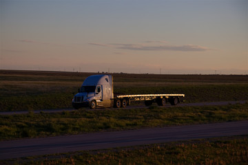 A white Freightliner Cascadia pulls an empty flatbed trailer down a rural US Highway during sunset hours. All visible trademarks and markings have been removed.