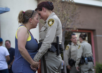 Cheri Rasmussen prays with Metro Police Lt. Roxanne McDarris in front of CiCi's Pizza during a community vigil for slain Metro Police officers in Las Vegas
