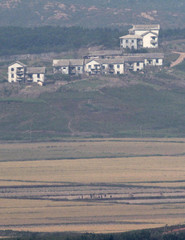 North Koreans harvest rice on fields in a village in North Korea's Kaepoong county in this picture taken from a South Korean observation post near the demilitarised zone separating the two Koreas in Paju