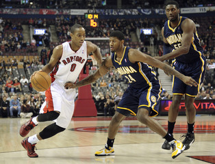 Raptors forward DeRozan goes to the basket against Pacers defenders George and Hibbert during their NBA basketball game in Toronto
