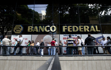 People queue outside a Banco Federal branch in Caracas