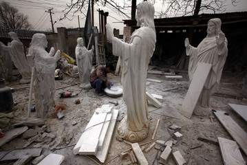 A sculptor works while surrounded by statues of Jesus Christ at an outdoor workshop in the town of Dangcheng in Quyang county