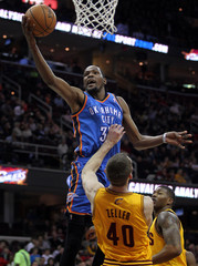 Oklahoma City Thunder's Kevin Durant puts up a shot over Cleveland Cavaliers Tyler Zeller during the first quarter of their NBA basketball game in Cleveland