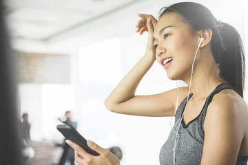 Asian woman in sportswear listening to the music with her cell phone at the gym.