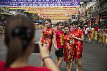 Women wearing traditional red clothes celebrating the Chinese Lunar New Year have their picture taken in Bangkok's Chinatown