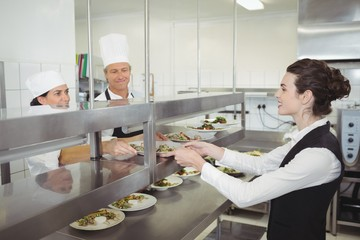 Chef handing food dish to waitress at order station