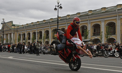 A biker and a woman demonstrate their skills on Nevsky Avenue in St. Petersburg