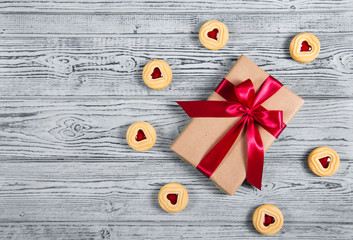 Gift box with satin bow and cookies with marmalade in the shape of heart. A romantic gift. Present on a gray background. Top view.