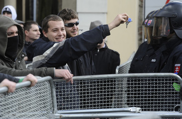 """A protester holds up keys to the face of a police officer during protest """"Gorilla"""" at National Council of the Slovak Republic in Bratislava"""