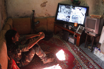 A Free Syrian Army fighter watches surveillance camera footage inside a house in Aleppo