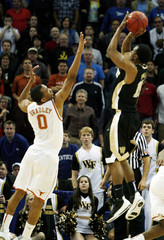 Wake Forest's Smith shoots over Texas' Bradley while scoring on a last second shot to defeat Texas in overtime during their Division I men's NCAA basketball tournament game in New Orleans