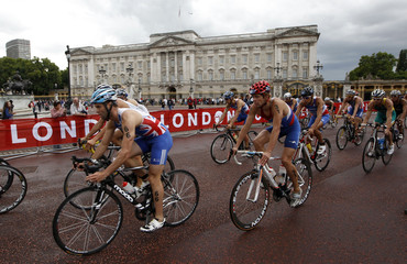 Triathletes cycle past Buckingham Palace on the 2nd stage of the men's Triathlon ITU World Championship at Hyde Park in London