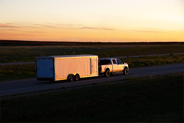 A white pickup truck pulls a small white box trailer down a rural highway during sunset hours. All visible markings and trademarks have been removed.
