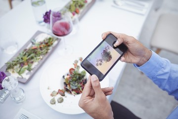 Man taking picture of food from mobile phone