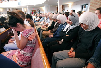People pray during an interfaith vigil for the victims of the Tennessee shooting, at Olivet Baptist church in Chattanooga