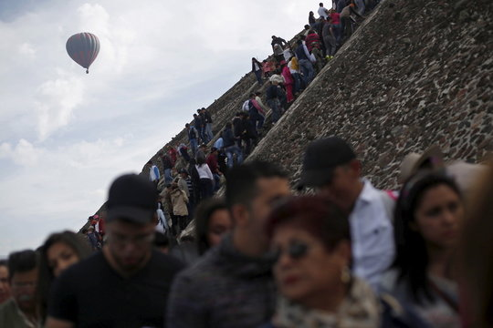 A hot air balloon floats past people standing in line to climb the Pyramid of the Sun and welcome the spring equinox in the pre-hispanic city of Teotihuacan, on the outskirts of Mexico City