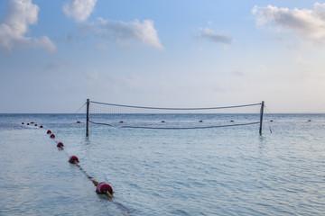 beach volleyball net in the ocean near the beach