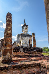 Ancient Buddha statue sitting among the ruins under the bright sky of Wat Maha That temple in Sukhothai Historical Park is an old city and famous tourist attraction of Sukhothai Province, Thailand