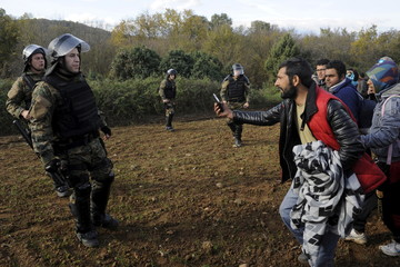 Macedonian police officers block stranded migrants as they attempt to cross the Greek-Macedonian border, near Gevgelija