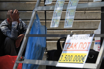 A man begs behind a lottery stand in Athens' Constitution (Syntagma) square