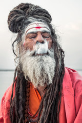 Portrait of sadhu smoking in the boat, Varanasi, India.