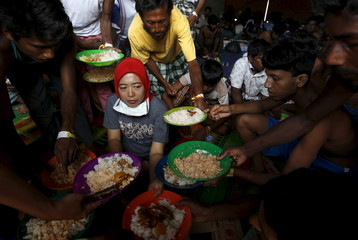 Bangladeshi migrants, who recently arrived in Indonesia by boat, raise up their plates to ask for more food, as breakfast is served by An Indonesian volunter at a shelter in Kuala Langsa