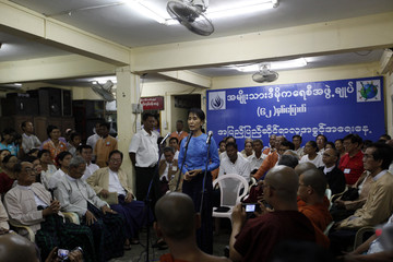 Myanmar's pro-democracy leader Suu Kyi talks with families of political prisoners during a ceremony to mark Human Rights Day in Yangon