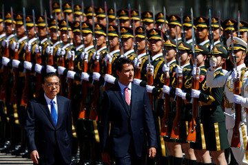 Chinese Premier Li Keqiang and Canadian Prime Minister Justin Trudeau inspect the honour guard at the Great Hall of the People in Beijing
