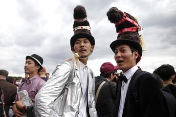Japanese spectators wearing funny hats attend the Qatar Prix de L'Arc de Triomphe at the Longchamp horse racetrack near Paris