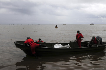 Rescue workers arrive at the beach after picking up from the ocean more bodies in Sabana de La Mar