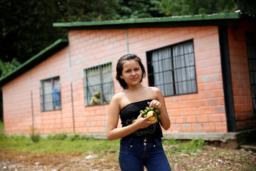 Iznaga holds mangoes and other tropical fruits while posing for a picture next to her house in La Fria
