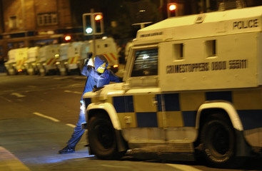 A young demonstrator attacks an armoured police vehicle during a stand-off between loyalist and nationalist demonstrators in east Belfast