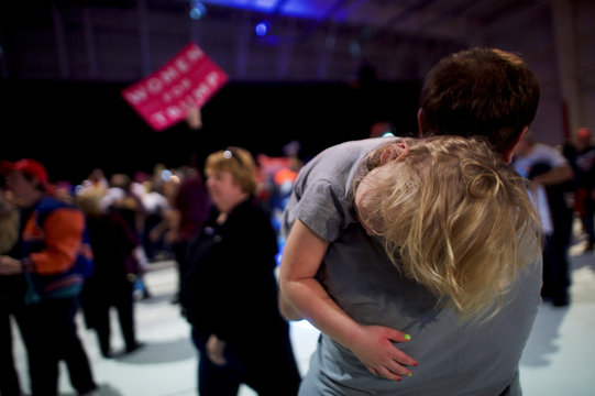 A boy rests on his father's shoulders as the U.S. Republican presidential nominee Donald Trump holds a rally at Atlantic Aviation in Moon, Pennsylvania