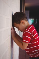 Side view of sad boy leaning on wall