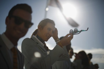 Australian Olympic team beach volleyballer Louise Bawden adjusts her hair in the reflection of her sunglasses during an official unveiling ceremony of Australia's Olympic team uniforms at Sydney's Bondi Beach