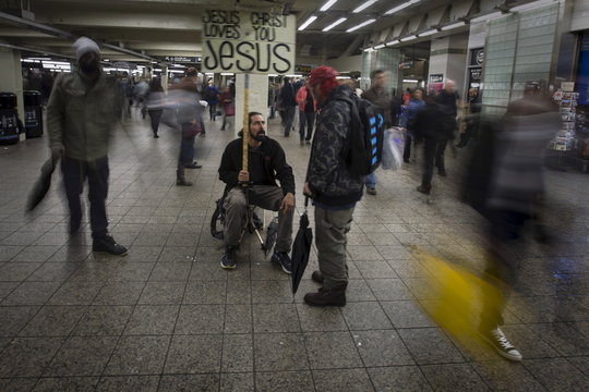 Arias sits in the Times Square subway station talks to a man about religion as commuters rush past in the Manhattan borough of New York