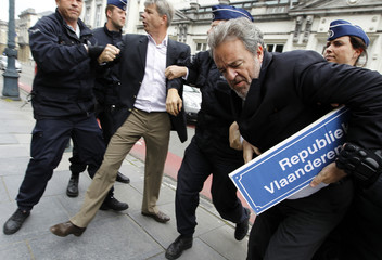 """Gerolf Annemans and a party member are arrested by police officers after changing a street sign with a sign reading """"Republic of Flanders"""" during a protest in Brussels"""