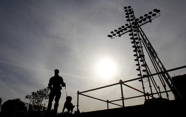 A policeman and his dog are silhouetted as they patrol near a cross at the Colosseum in Rome