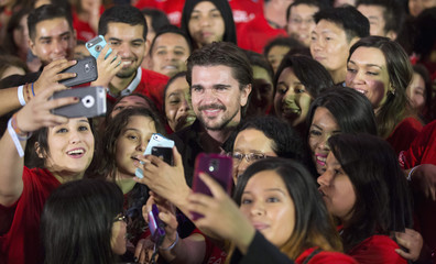 """Colombian singer Juanes poses with fans after the premiere of """"McFarland, USA"""" at El Capitan theatre in Hollywood"""