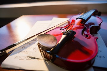 Close up of violin with sheet music on table