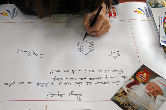A child draws Christmas wishes on world's longest letter addressed to Santa Claus during a Guinness World Record attempt in Pantelimon