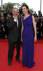 """French economist Attali poses with actress Bouquet as they arrive on the red carpet for the screening of the film """"Sleeping Beauty"""" at the 64th Cannes Film Festival"""