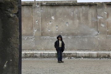 A boy stands near a riddled wall of his school, due to what activists said was an airstrike carried out yesterday by the Russian air force in Injara town, Aleppo countryside, Syria
