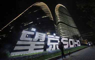 A woman walks her dog past a logo in front of Wangjing SOHO, on the opening day of the compound, in Beijing
