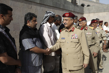 Yemen's Defense minister, Maj. Gen. Mohammed Nasser Ahmed shakes hands with family members and friends of slain Major General Salem Ali Qatan, the commander of military forces in the south of Yemen, in Sanaa