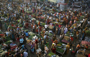 Customers shop at an open air vegetable and fruit market in the western Indian city of Ahmedabad