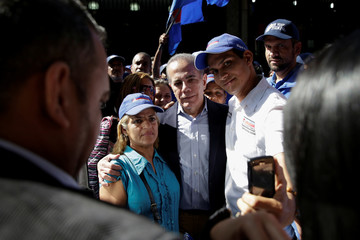 Former Venezuelan presidential candidate Manuel Rosales poses for a photo with supporters after being released outside the courthouse in Caracas