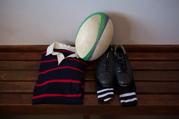 Rugby ball and clothes with shoes on bench in locker room