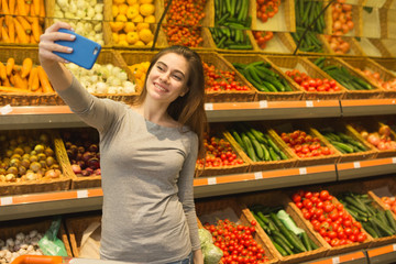 Attractive young woman using her smart phone while shopping at the supermarket
